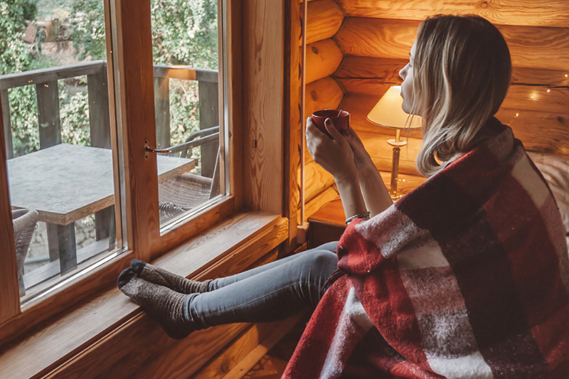 girl sipping coffee looking out window